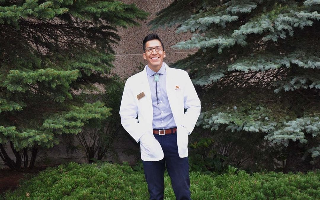 Photo of Casey Smith, med student, posing for a photo in front of some evergreen trees.