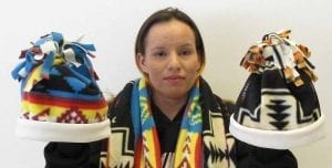 GED student displays hats and scarves she made.