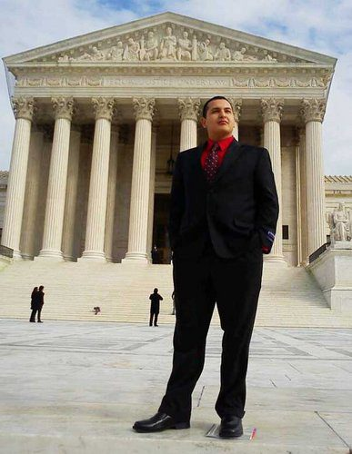 student standing outside the Supreme Court in a business suit