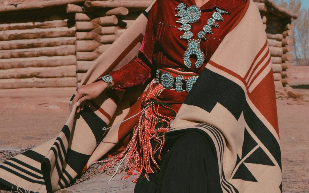 Shondina Lee models the new blanket outside of a Navajo Hogan.