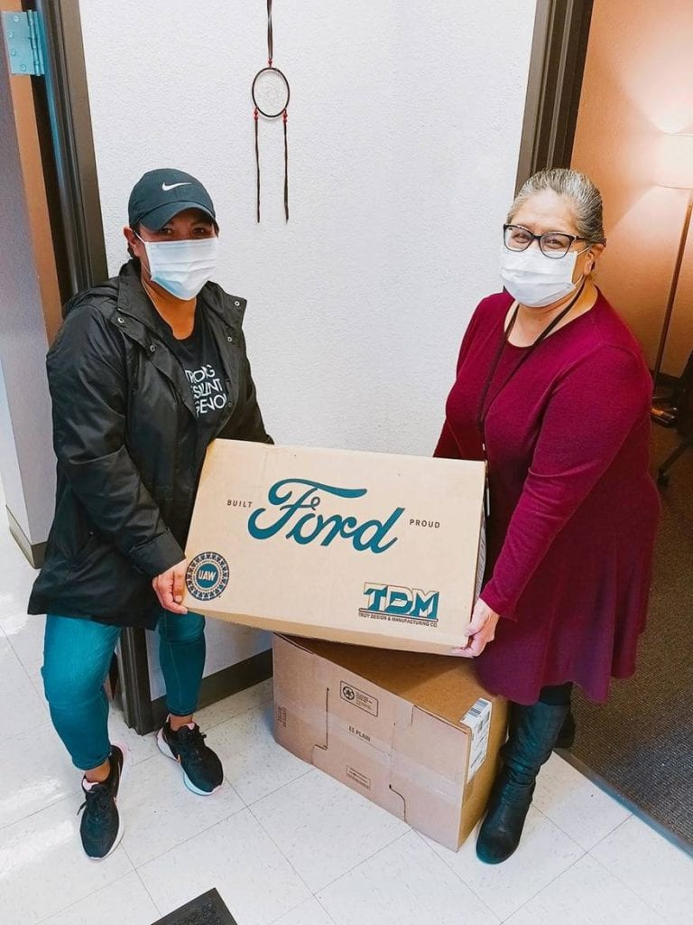 Adrianne Maddux, Denver Indian Health and Family Services (DIHFS) Executive Director (right) is assisted by Crystal Hedgepeth (left), an American Indian College Fund staff member and DIHFS board member, with a delivery of personal protective equipment.
