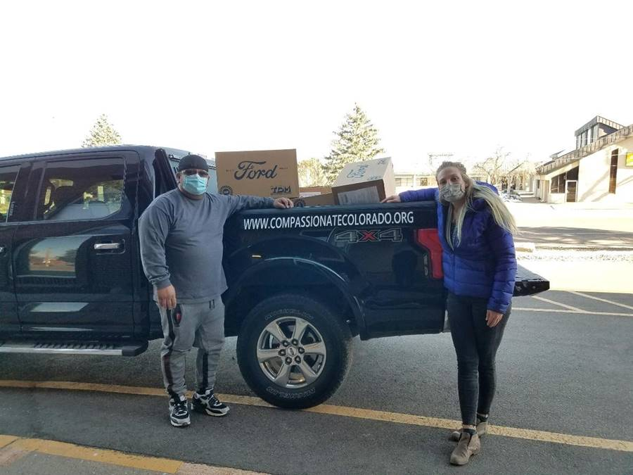 Justine Lenninger of the American Indian College Fund (right), helps load PPEs into a truck for Lucas Garcia, co-founder and Executive Director of Compassionate Colorado (left).