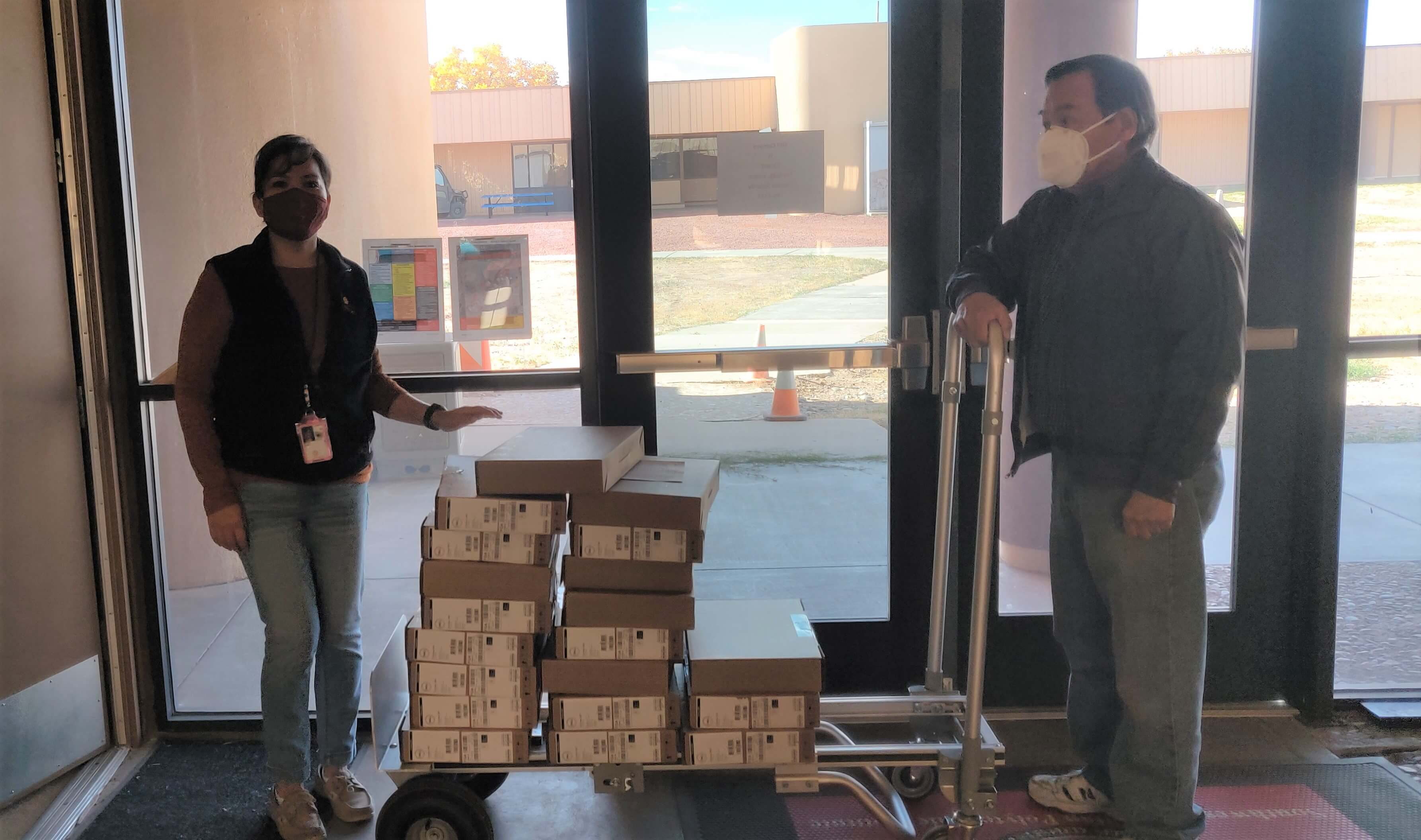 SIPI staff, Bobbi Brown and Dennis Dyer, mail out laptops to HSE students